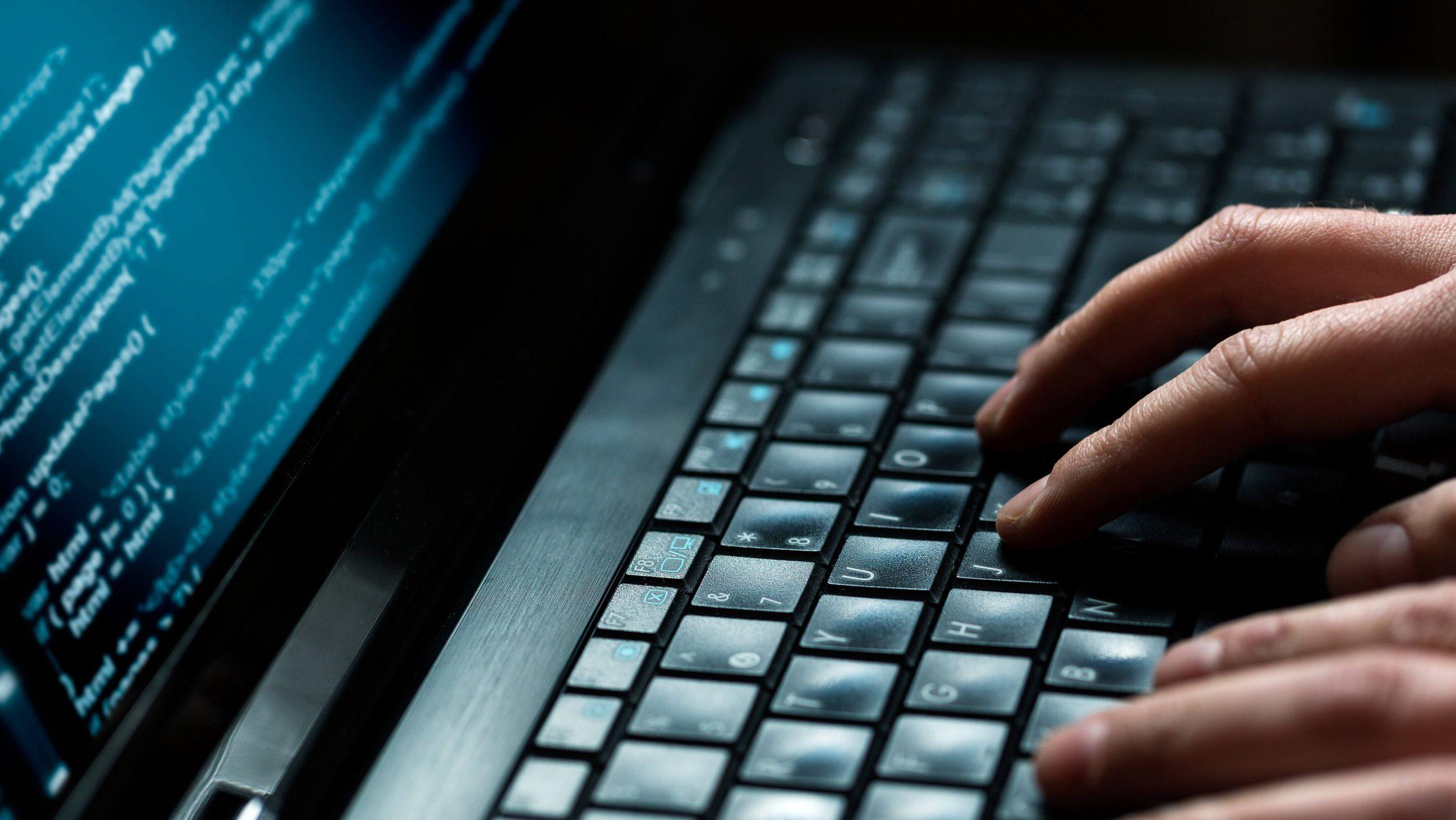 close up og hands on laptop keyboard typing code