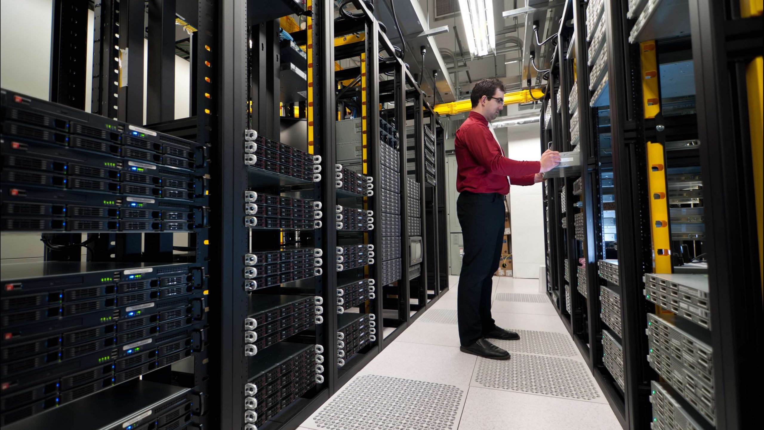 male tech inserting a new server rack into a cabinet in a data center