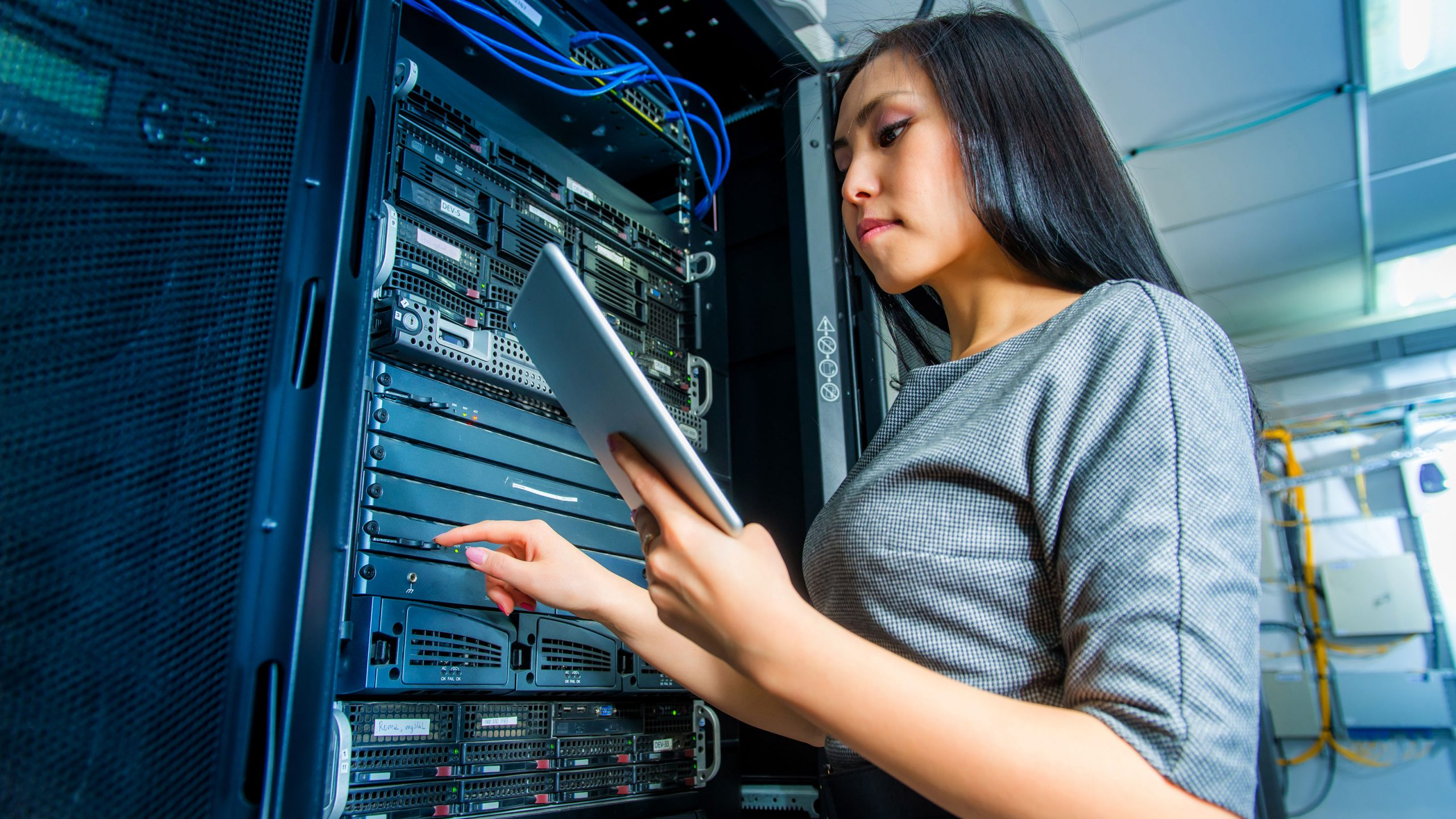 woman checking status of server in data center